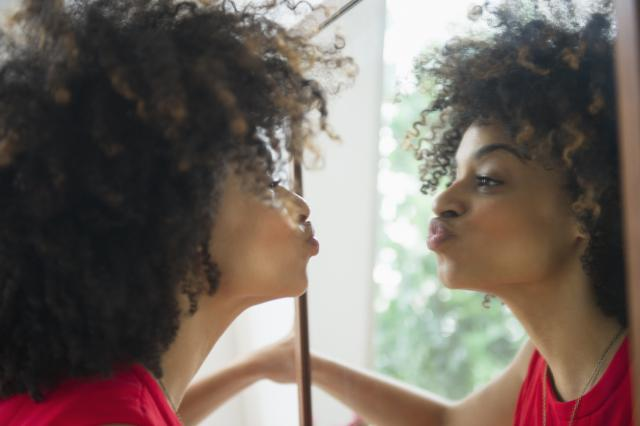 natural hair girl kissing herself in the mirror